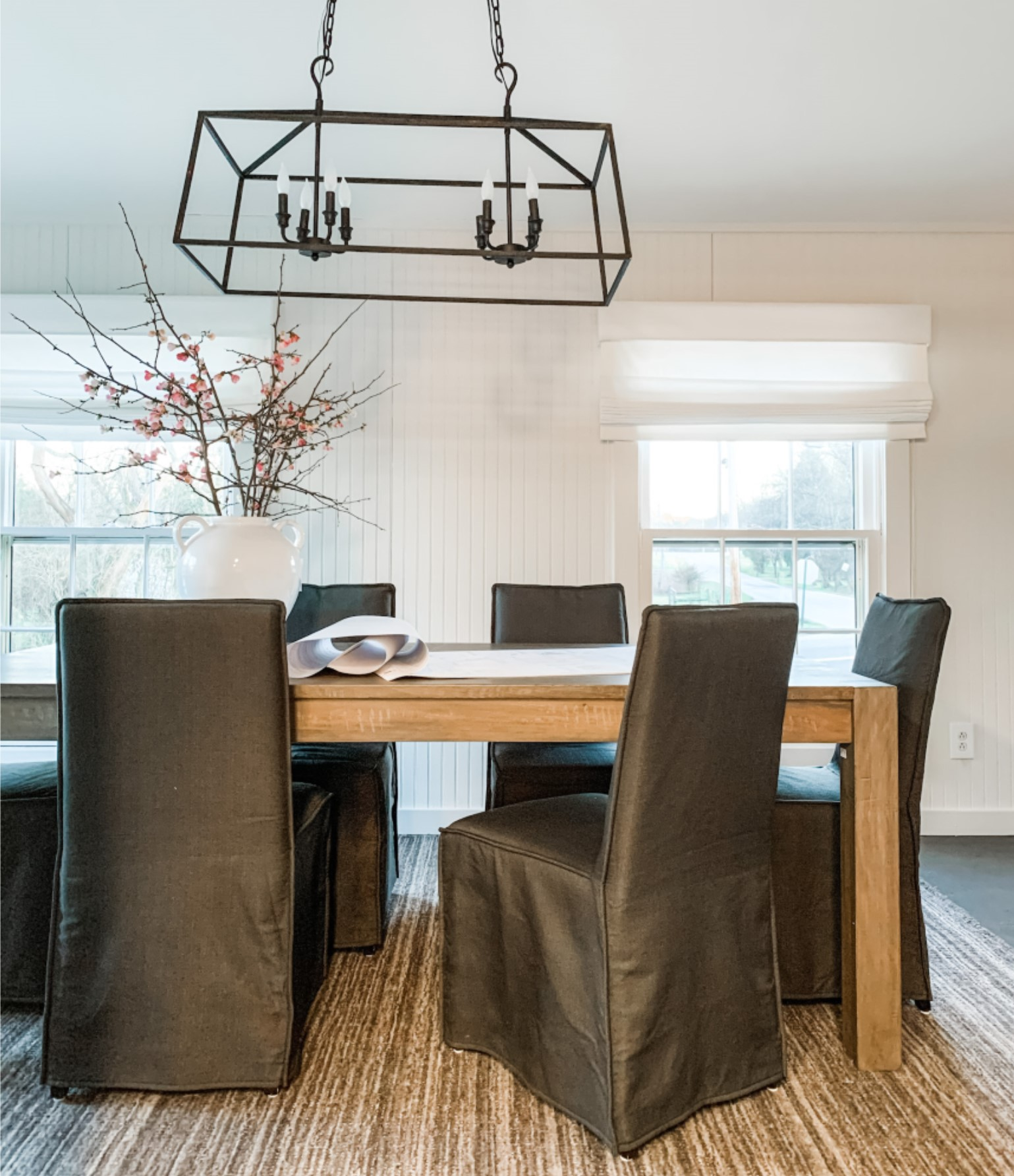 Design studio conference room with linear chandelier, wood conference table, and gray upholstered chairs